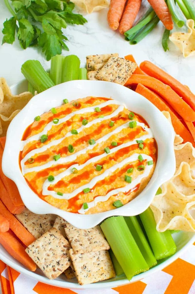 slow cooker buffalo chicken dip and a platter of veggies, crackers and chipsslow cooker buffalo chicken dip and a platter of veggies, crackers and chips