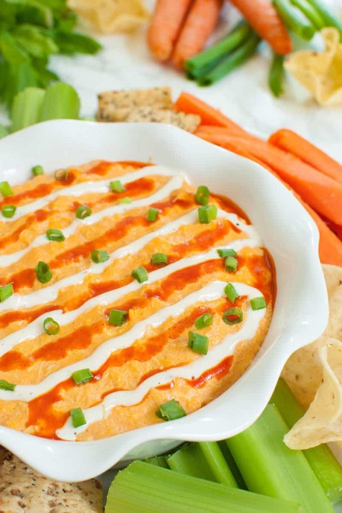 White dish of slow cooker buffalo chicken dip topped with green onions, ranch and buffalo sauce