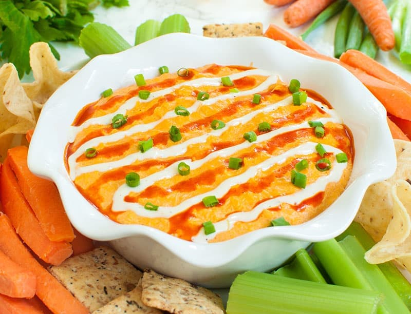 slow cooker buffalo chicken dip with a platter of dippers