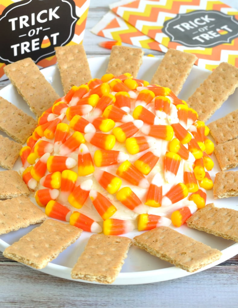 Candy corn cheesecake cheese ball recipe that features white, orange, and yellow layers just like the candy. This is a great fall dessert for Halloween.