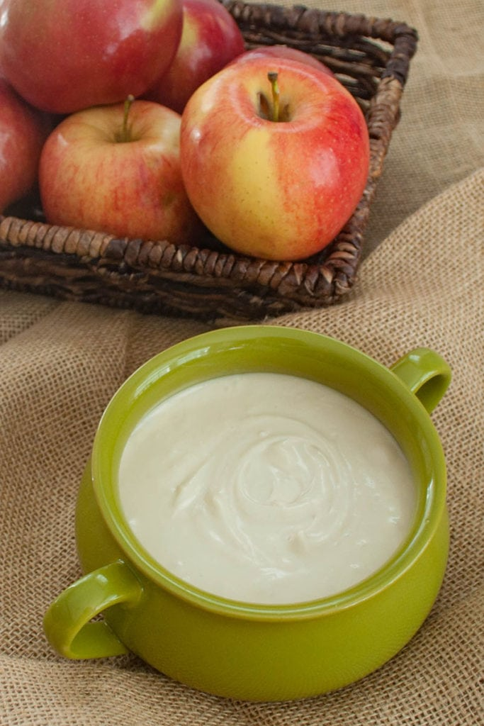 green bowl with maple dip and a basket of apples