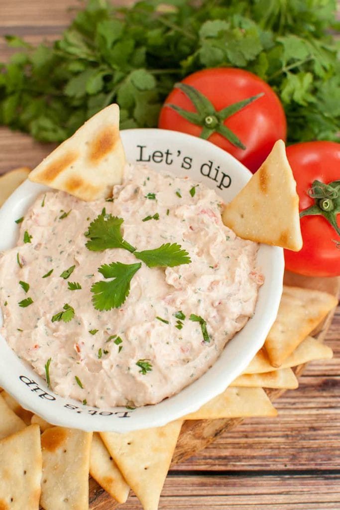 bowl of texas love dip surrounded by crackers, 2 tomatoes and a bunch of cilantro