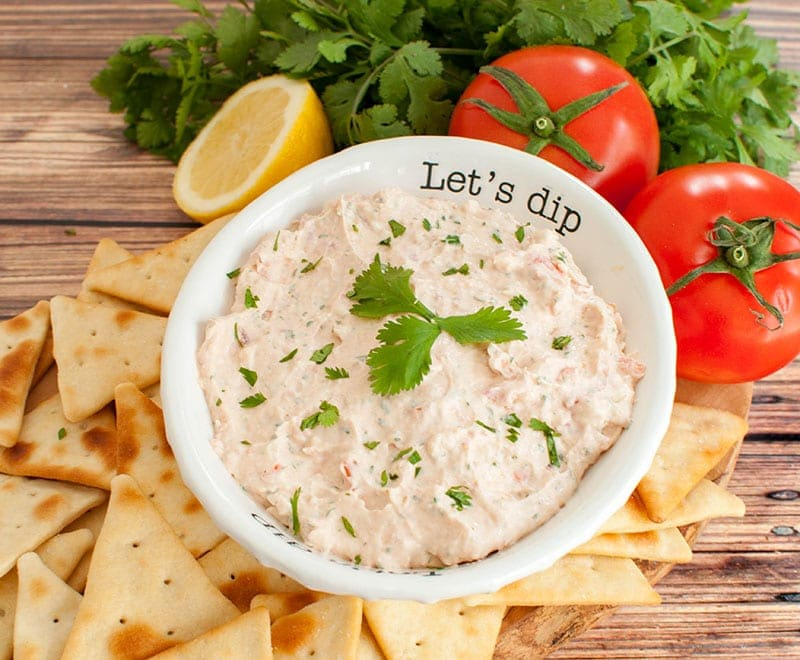 white bowl of texas love dip topped with 3 cilantro leaves