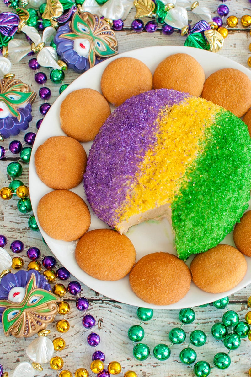 purple, gold and green cheese ball on plate surrounded by beads