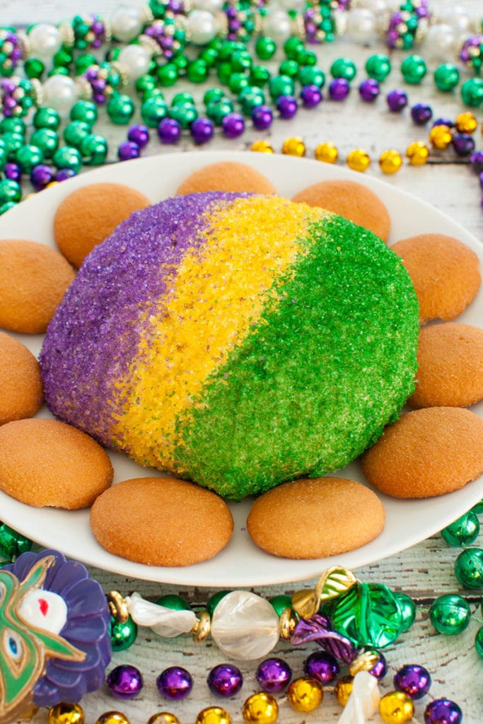 purple, gold and green dip on white plate surrounded by beads