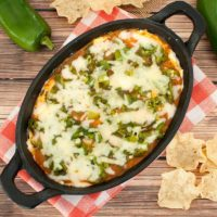 Chile Relleno Dip in cast iron dish on orange and white napkin