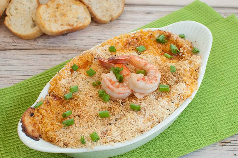 shrimp dip in a white dish topped with 2 shrimp