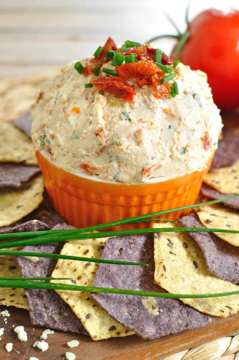 orange bowl with sun-dried tomato dip topped with sun-dried tomatos