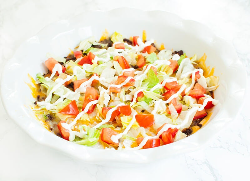 White pie dish of taco dip with meat topped with lettuce, tomato, cheese and sour cream