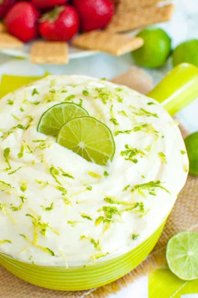 bight green bowl of key lime pie dip with lime slices on top