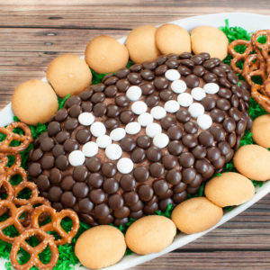 Oval platter with a chocolate dessert cheese ball football and pretzels and vanilla wafers