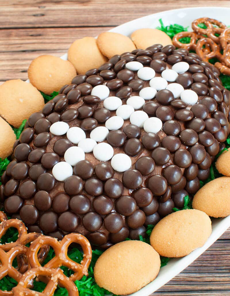 A football shaped chocolate dessert cheese ball with pretzels and vanilla wafers