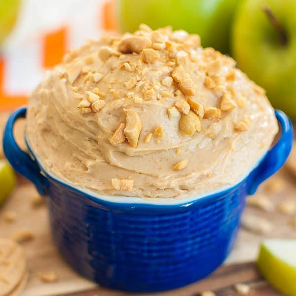 Green apples and blue bowl of peanut butter dip