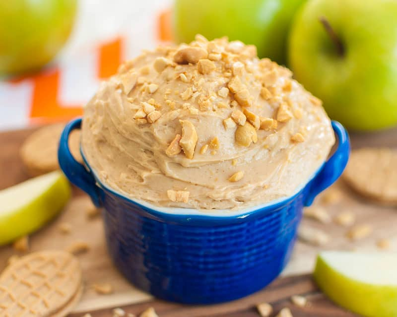 Bowl with peanut butter apple dip topped with crushed peanuts
