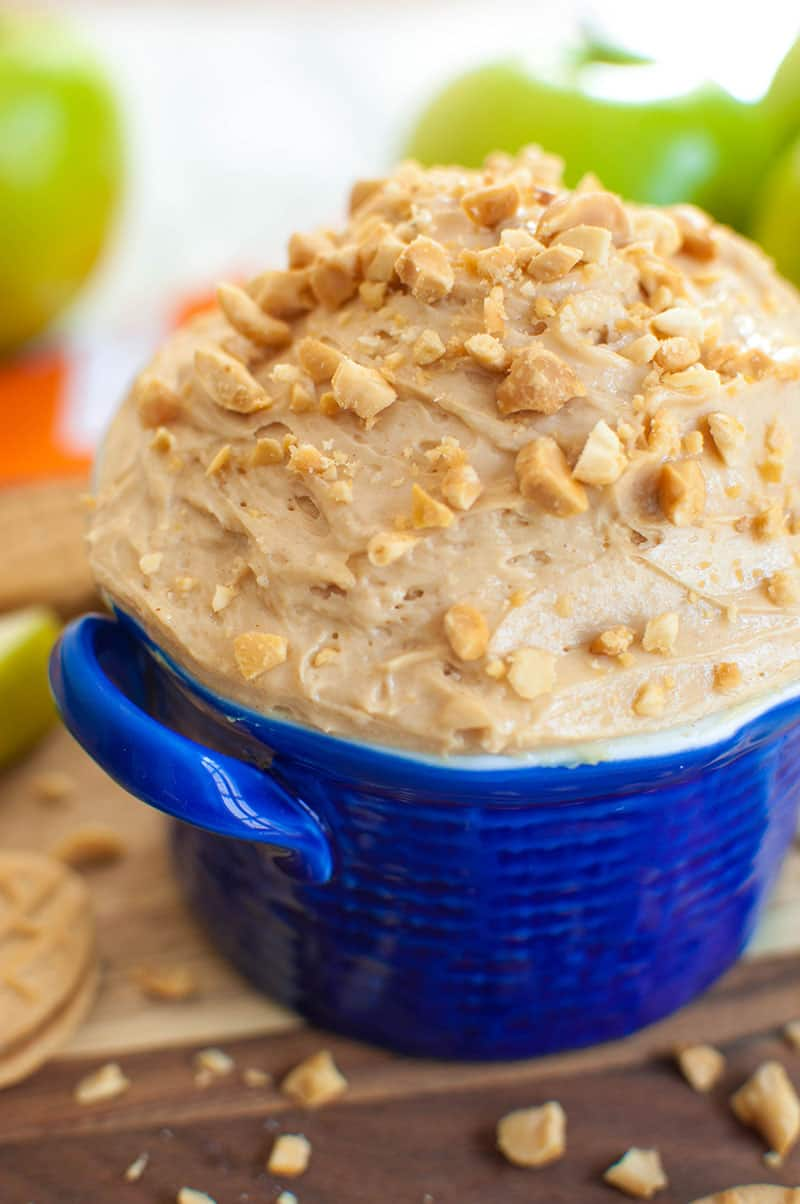 blue bowl of peanut butter apple dip with green apples