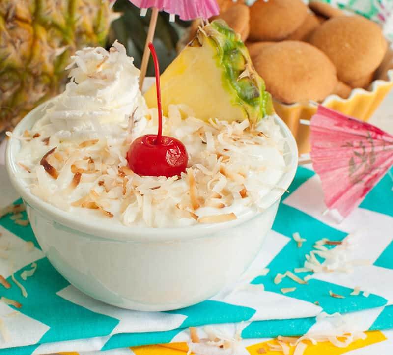 Bowl of pineapple dip with coconut topped with a cherry aka Pina Colada Dip