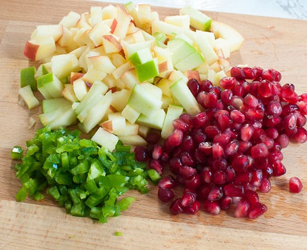 diced apples and jalapenos on a cutting board with pomegranate seeds