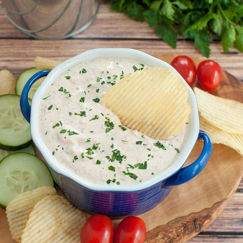 bowl of sour cream dip on a serving board with chips and veggies