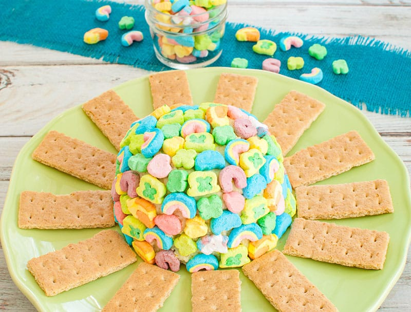 Lucky Charms Cheesecake Cheese Ball covered in lucky charm marshmallows on green platter