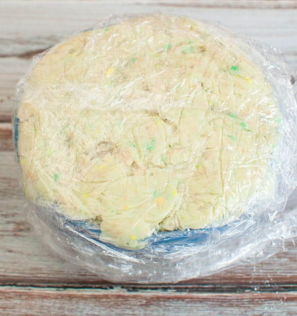 lucky charms cheesecake cheese ball mixture in small bowl wrapped in plastic wrap