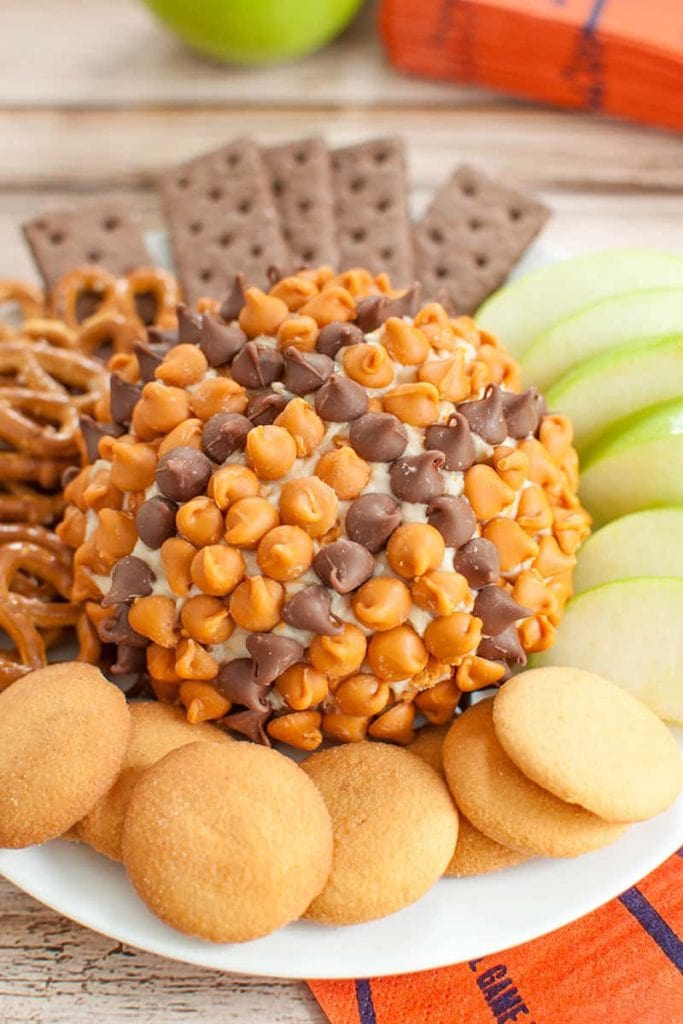 A caramel dessert cheese ball decorated like a basketball on a plate with dippers