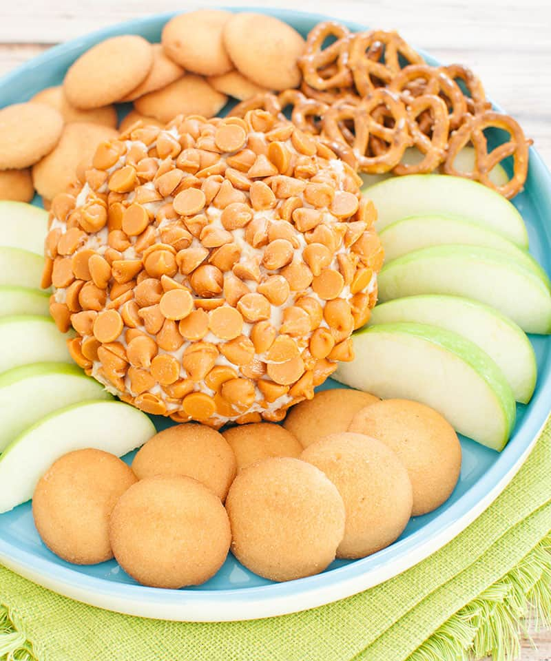 no bake caramel cheese ball covered in salted caramel chips on a blue platter