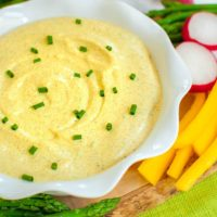 yellow curry dip topped with chives on a board with veggies