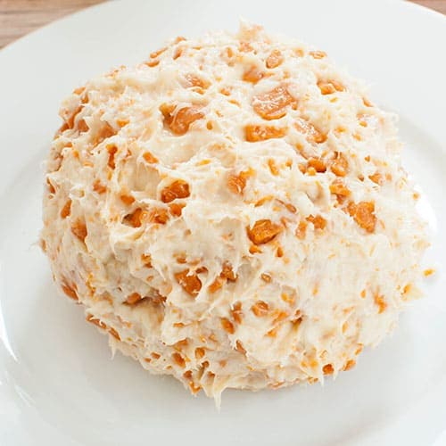 uncovered caramel cheese ball on a white plate