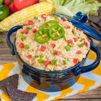 blue bowl of mexican corn dip with blue tortilla chips