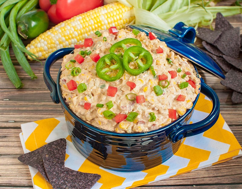 blue bowl of mexican corn dip on yellow and white napkin
