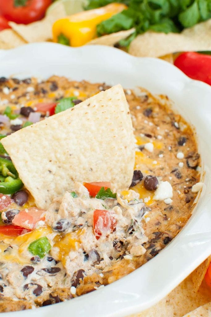 white dish of black bean dip with a tortilla chip dipped in