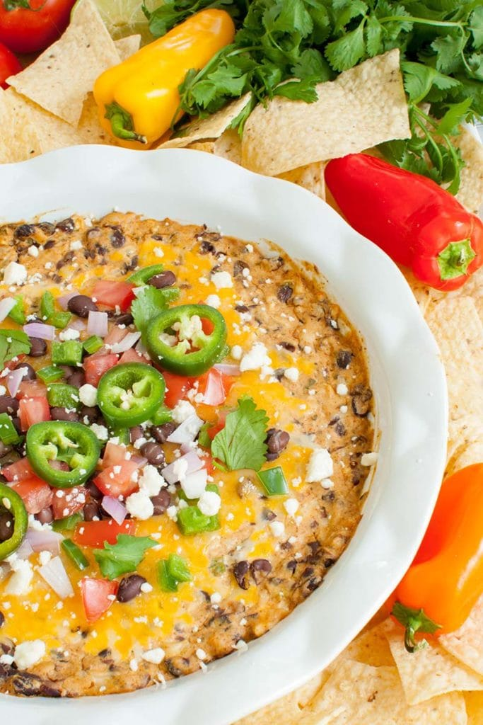 white dish of black bean dip with melted cheese on top