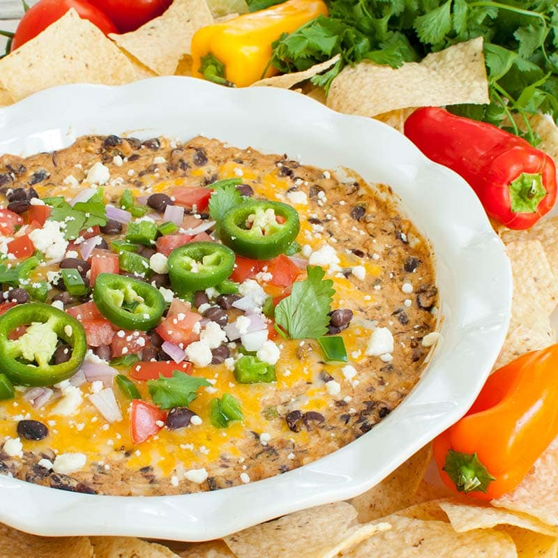 black bean dip in a white dish topped with melted cheese and jalapenos