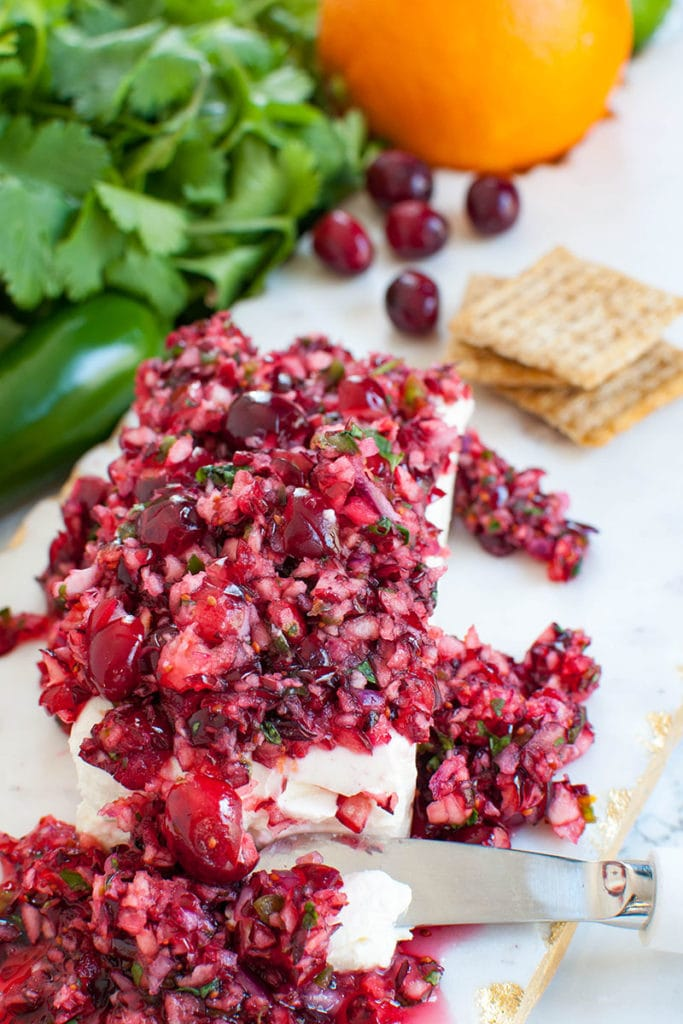 cranberry salsa with cream cheese on a white marble board