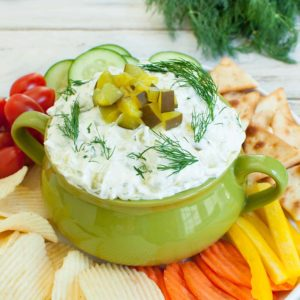 green bowl with dill pickle dip topped with chopped pickles