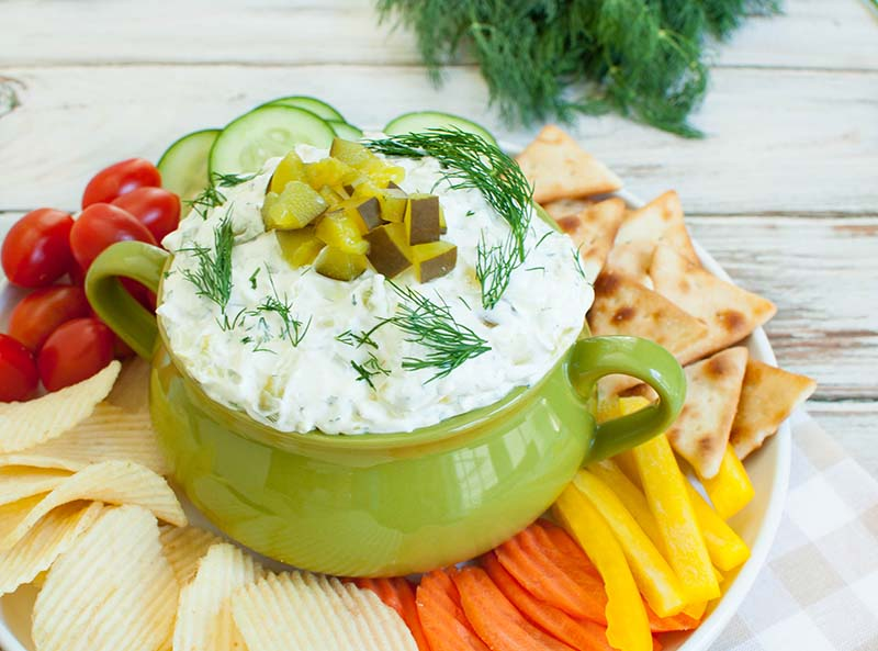 green bowl of dill pickle dip on a platter of veggies