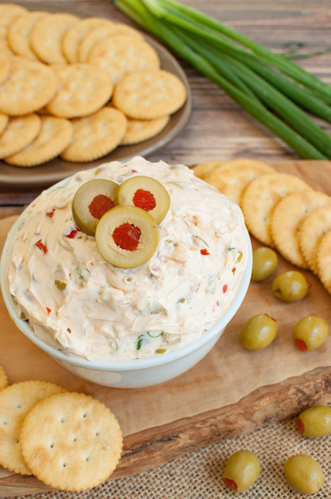 olive dip in white bowl with crackers