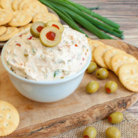 olive dip in a bowl with a plate of crackers