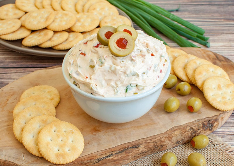 olive dip in bowl on a wood cutting board