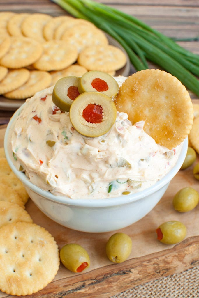 cracker dipped into olive dip