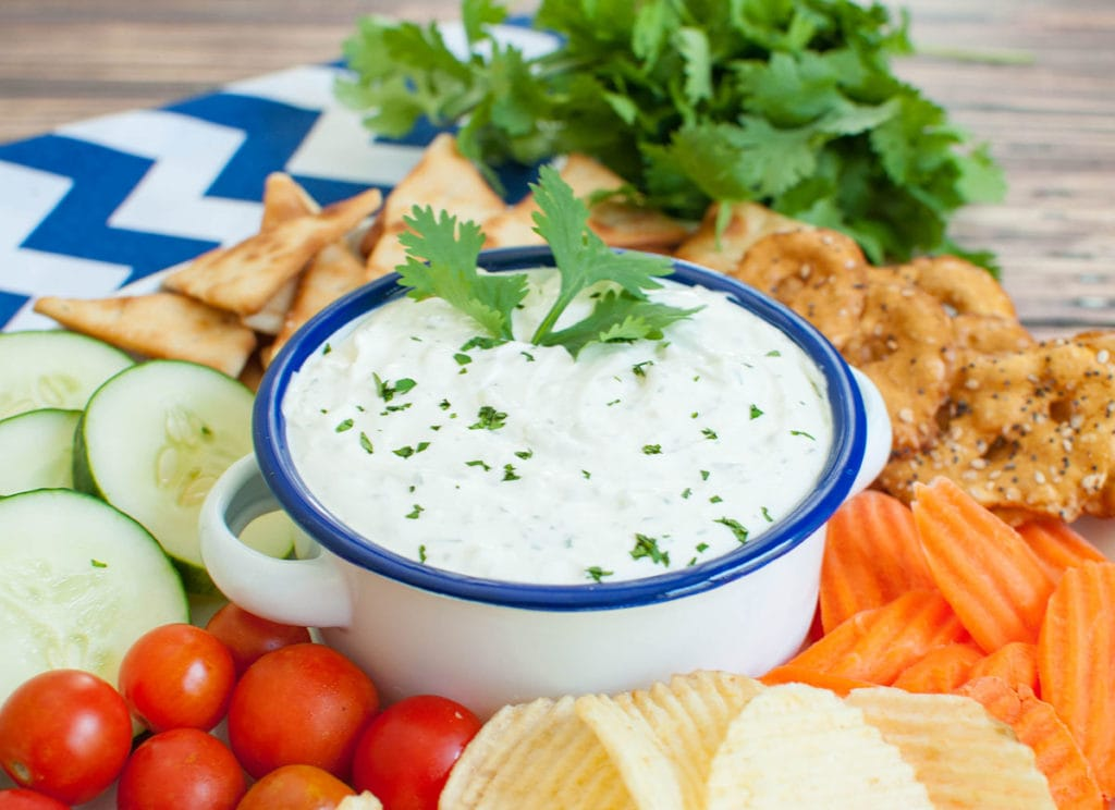 veggie and chip platter with white and blue bowl of dip