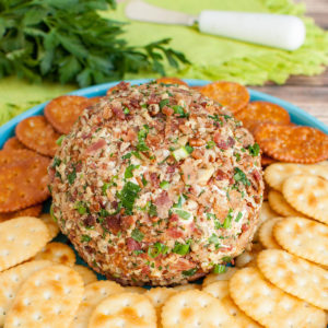 banch ranch cheese ball on teal blue platter with crackers