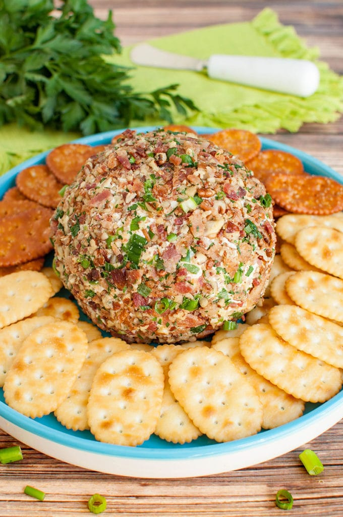 cheese ball with crackers on teal platter
