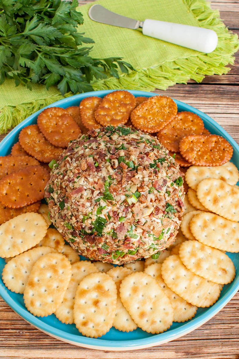 banch ranch cheese ball on teal blue platter with crackers and pretzels