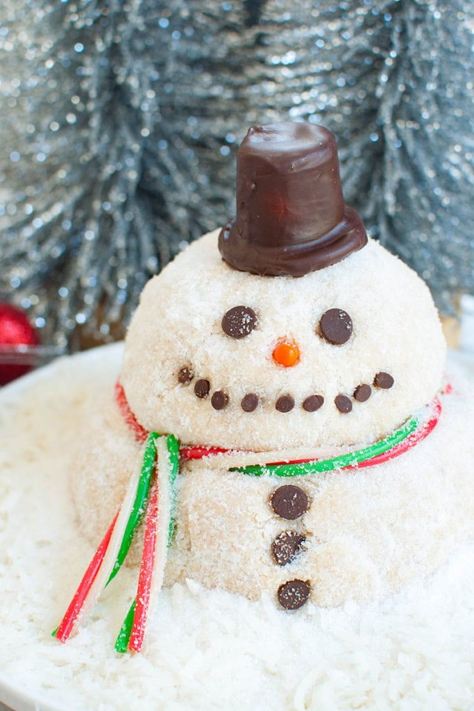 dessert cheese ball shaped like a snowman and decorated on a platter