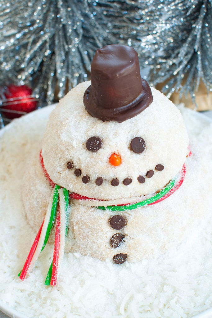 snowman dessert cheese ball decorated with a hat and scarf