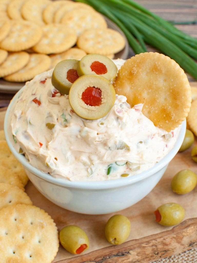 olive dip in white bowl with a cracker dipped in