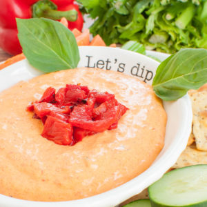 white bowl with roasted red pepper dip topped with peppers