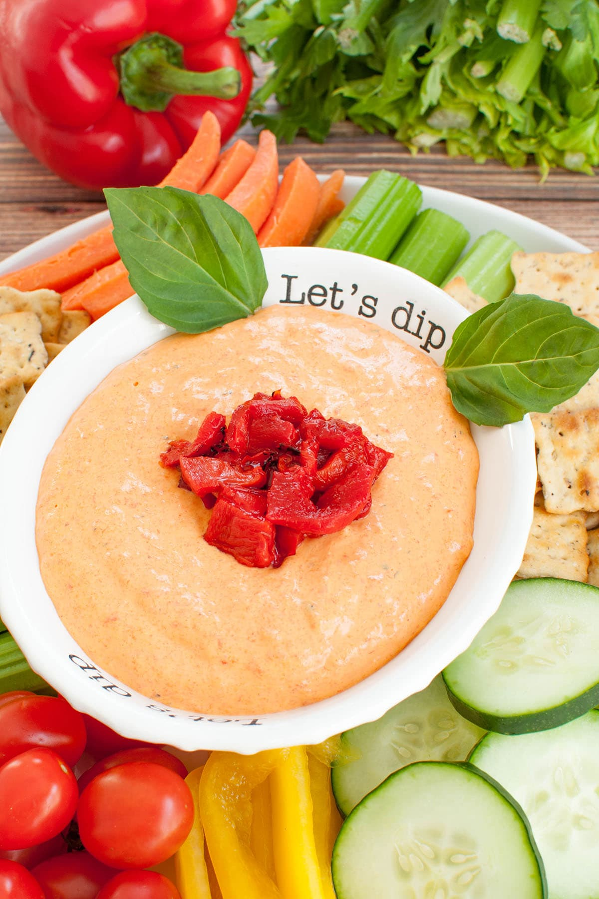 roasted red pepper dip in a white bowl on a platter of veggies