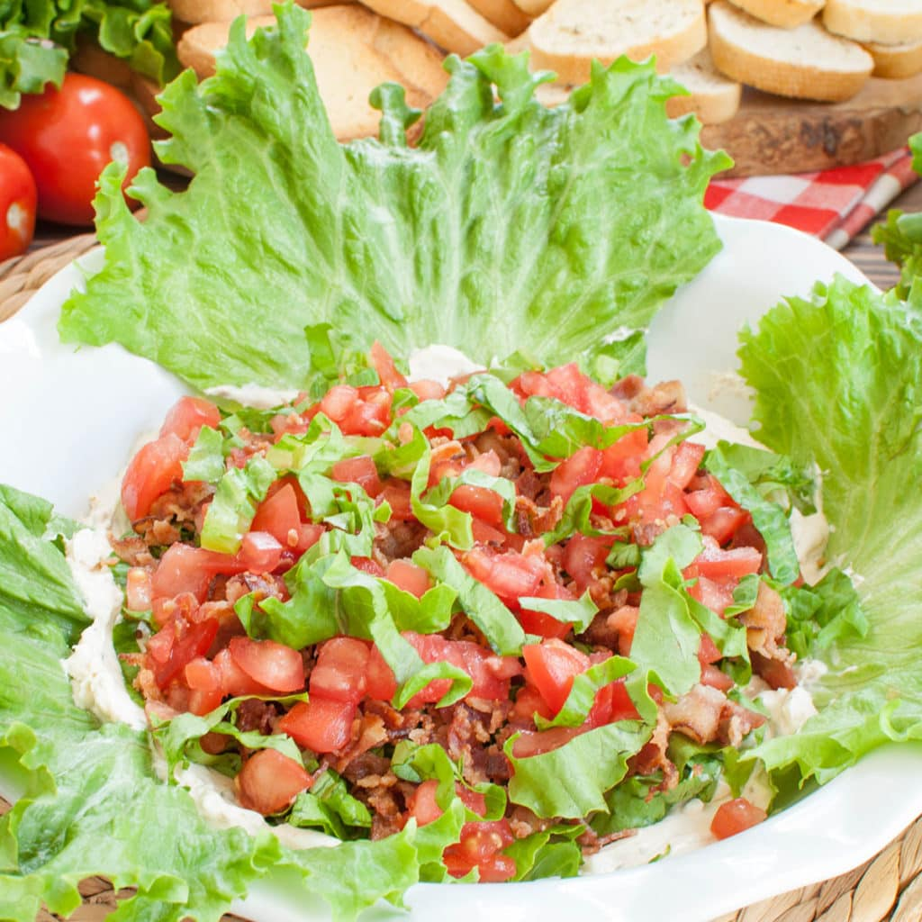 white baking dish of blt dip garnished with lettuce leaves